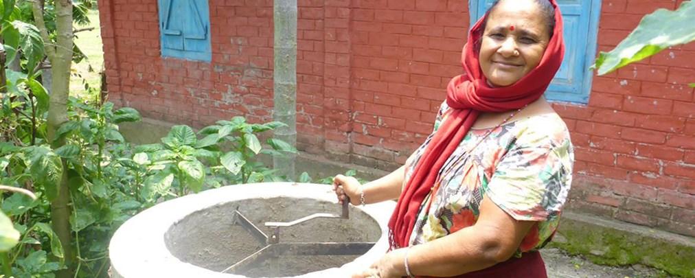 """Nepalesische Frau bei der Herstellung des """"Slurry"""" – dieser vergärt in der Biogasanlage"""