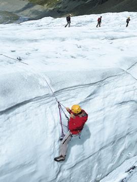 Eine Seilschaft am Gletscher und ein Bergsteiger, der sich aus einer Spalte befreit. Hoffentlich sind beide richtig angeseilt.