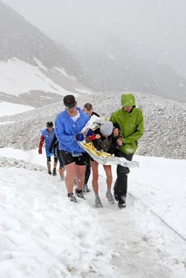 Helfer der Bergwacht stützen einen völlig erschöpften Aktiven. Bild: dpa.