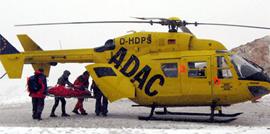Helfer laden auf der Zugspitze einen unterkühlten Extremsportler in einen Rettungshubschrauber. Bild: dpa.