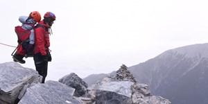Bergsteiger trägt gelähmte Frau auf den Olymp